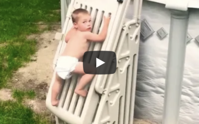 toddler climbs pool ladder